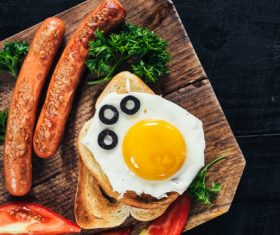 Omelette and fried sausage on cutting board Stock Photo