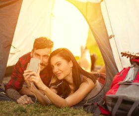 Self-portrait with mobile phone in camping tent Stock Photo