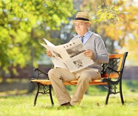 Senior man sitting on park bench reading newspaper Stock Photo