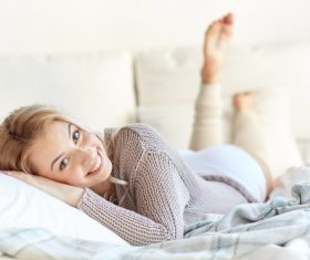 Smiling woman lying in bed Stock Photo