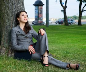 Stock Photo Businesswoman sitting relaxed on the grass