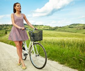 Stock Photo Girl pushing a bicycle on a country road 01
