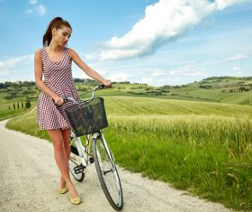 Stock Photo Girl pushing a bicycle on a country road 02
