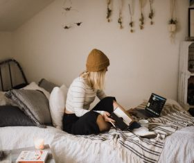 Stock Photo Girl sitting in bed studying
