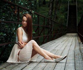 Stock Photo Girl sitting on the bridge