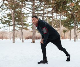 Stock Photo Man doing warm-up exercises on the snow