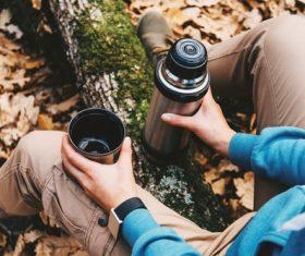 Stock Photo Man sitting on tree trunk holding thermos mug