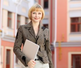 Stock Photo Smiling woman holding laptop