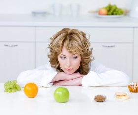 Woman choosing what to eat Stock Photo