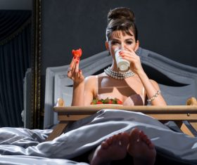 Woman drinking milk in bed Stock Photo