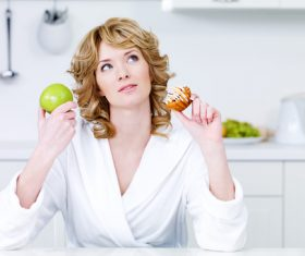 Woman holding apple and cake Stock Photo