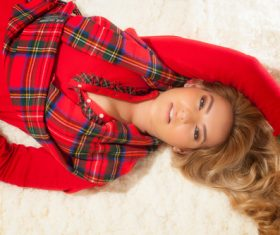 Woman in red costume lying on the carpet Stock Photo