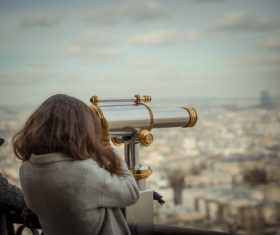 Woman looking at city landscape with telescope Stock Photo