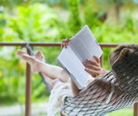 Woman lying in hammock reading book Stock Photo