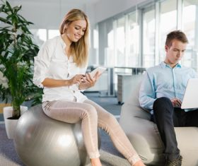 Woman sitting on fitness ball looking at mobile phone Stock Photo