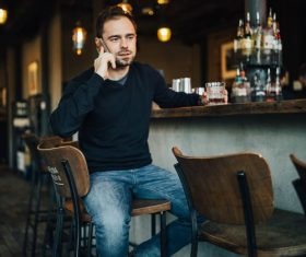 Young man drinking make phone call at the bar Stock Photo