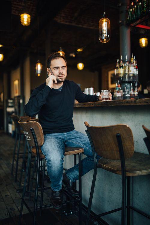Young man drinking make phone call at the bar Stock Photo