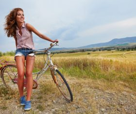 woman with vintage bike in a country road Stock Photo 01