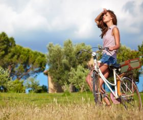 woman with vintage bike in a country road Stock Photo 03