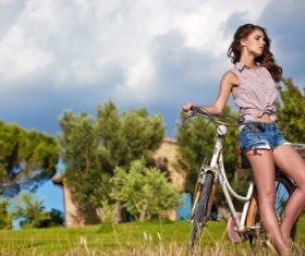 woman with vintage bike in a country road Stock Photo 04