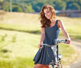woman with vintage bike in a country road Stock Photo 05