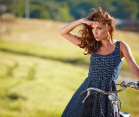 woman with vintage bike in a country road Stock Photo 06