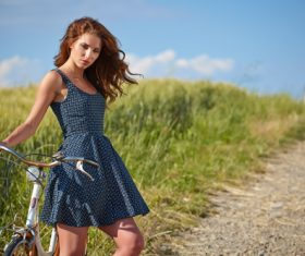 woman with vintage bike in a country road Stock Photo 07