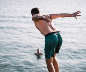 Back barefoot man jumped into the sea Stock Photo
