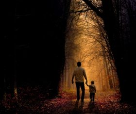 Father and son walking in the woods trail Stock Photo