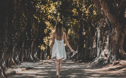 Girl holding slipper barefoot walking Stock Photo