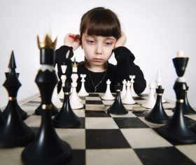 Little girl concentrates on playing Chess Stock Photo