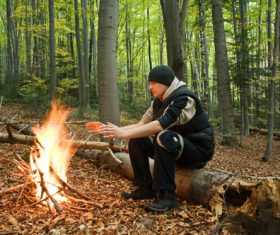Man in the wild roasting fire Stock Photo