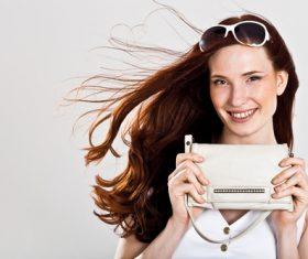 Smiling woman holding handbag Stock Photo