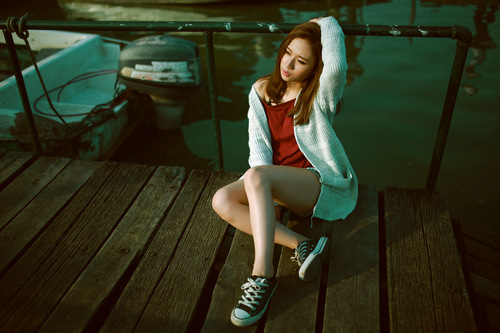 Stock Photo Charming girl sitting on the dock
