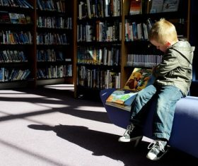 Stock Photo Children reading comic books in the library