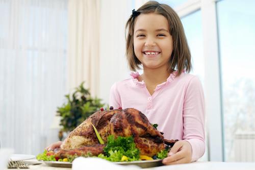 Stock Photo Little girl holding festive sultry turkey