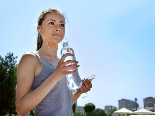 Stock Photo Pretty girl holding bottle of mineral water