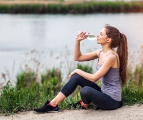 Stock Photo Pretty girl sitting on the ground for rest and water