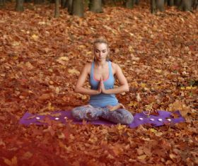 Stock Photo Woman practicing yoga in the autumn woods