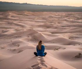 Stock Photo Woman sitting on desert sand dunes