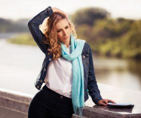 Stock Photo Woman standing on the bridge combing hair