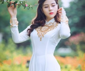 Stock Photo Woman wearing traditional Vietnamese white cheongsam fiddling with squid