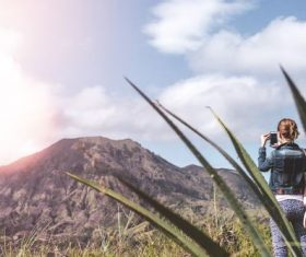 Stock Photo Women use smartphone to shoot volcano