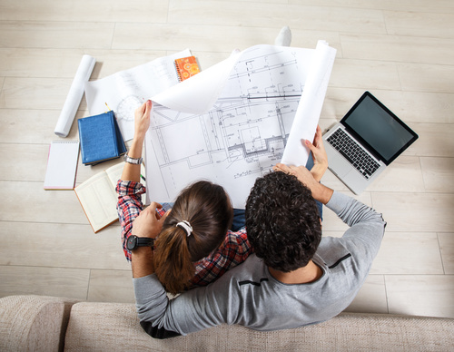 Stock Photo Young Couple Examing Blueprints of they New House 01