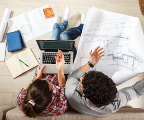 Stock Photo Young Couple Examing Blueprints of they New House 02
