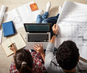 Stock Photo Young Couple Examing Blueprints of they New House 03