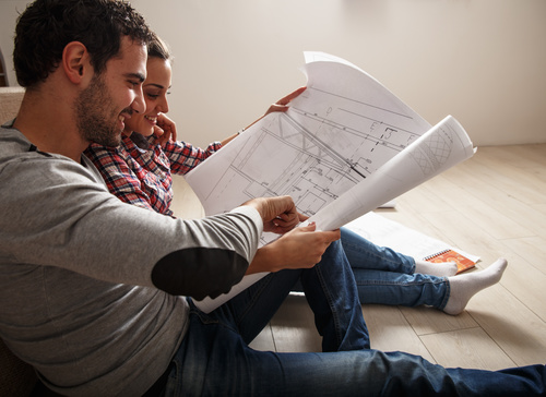 Stock Photo Young Couple Examing Blueprints of they New House 04