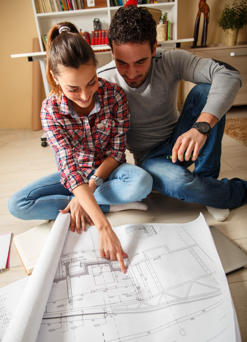 Stock Photo Young Couple Examing Blueprints of they New House 05