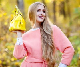 Woman in pink coat holds yellow handbag pose Stock Photo