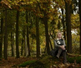 Woman sitting in the woods enjoying nature Stock Photo
